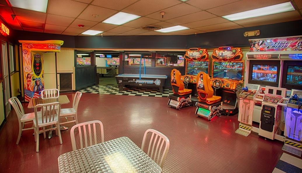 Snack bar Arcade and game room with air hockey table, racing arcade games, time crisis 4, and seating area