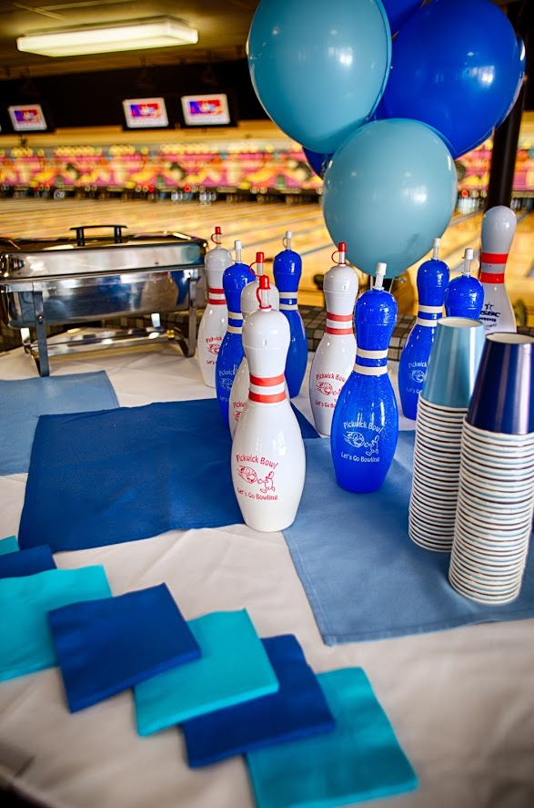 Beautiful birthday party table with party cups, napkins, food, birthday balloons, and bowling pins
